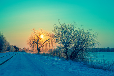 Early morning. Road along the covered with snow field at sunrise Stock Photo