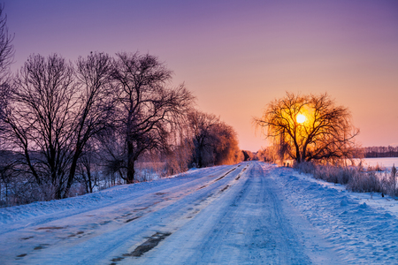 eventide: Early morning, road covered with snow at sunrise Stock Photo