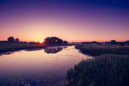 crick: Magical pink purple sunrise over the river. Misty morning, rural landscape, wilderness, mystical feeling Stock Photo
