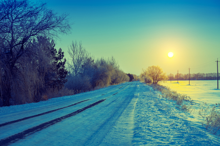 Early morning. Country road covered with snow at sunrise