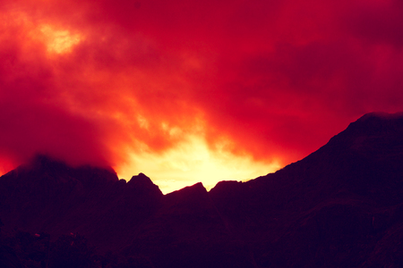 Mountain top outlined with cloudy sunset sky. Burned red sunset. Beautiful nature Norway. Lofoten islands. Reine