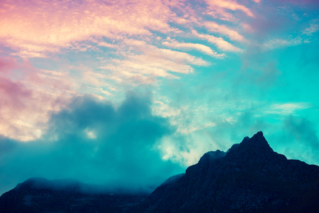 Mountain top outlined with cloudy sunset sky. Pink yellow sunset. Beautiful nature Norway. Lofoten islands. Reine