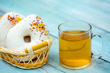 A glass of tea with donuts on a wooden table Stock Photo