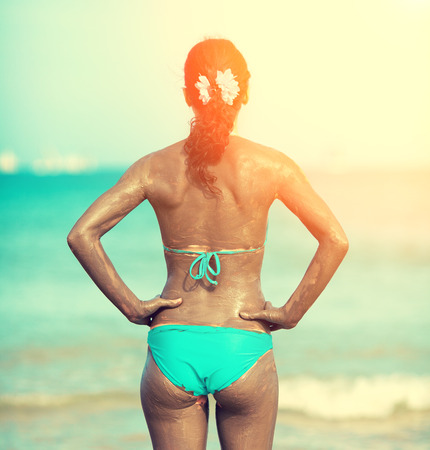A woman smeared with Dead Sea mud on the beach Stock Photo