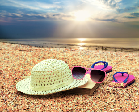 coquina: Beach scene. Sun straw hat, book, flip flop sandals and sunglasses lying on sea coquina shells on the beach at sunrise