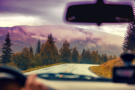curve road: Driving a car on the mountain road. Road among mountains with the dramatic stormy cloudy sky. Landscape. Beautiful nature of Norway.