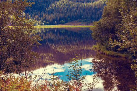 Rocky shore of the mountain lake in the misty autumn morning. Beautiful nature of Norway. Reflection in the lake