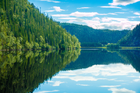 Rocky shore of the mountain lake. Beautiful nature of Norway. Sky reflection in a lake Stock Photo
