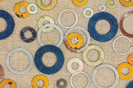 Abstract grunge background. Colorful metallic rings washers on blue wooden background