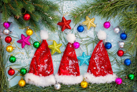 Christmas composition. Three little Santa Clauses hats lying on Christmas background with  fir tree branches, snow, stars and balls Stock Photo