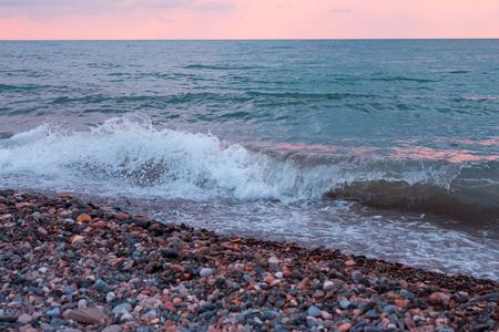 Pebbles sea beach at sunset