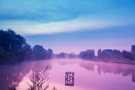 Presto la mattina, all'alba sul lago. Lago calmo prima dell'alba. Una mattina nebbiosa, un paesaggio rurale, un deserto, una sensazione mistica