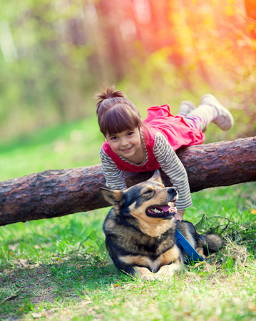 Happy little girl playing with the dog in the forest. Girl lying on the log Stock Photo