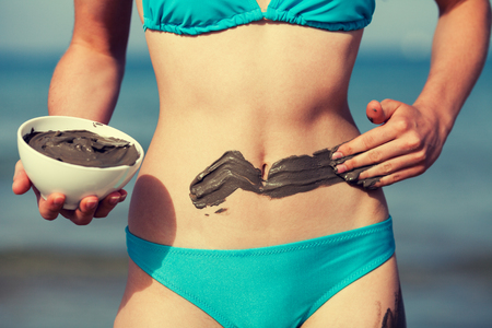 Woman smearing mud mask on the body on the beach