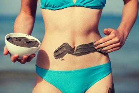 Frau , die Schlamm-Maske auf dem Körper am Strand