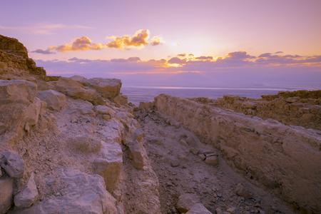 Beautiful purple sunrise over Masada fortress. Ruins of King Herods palace in the Judaean Desert Stock Photo