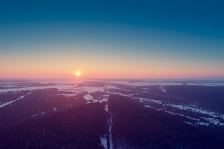 Aerial evening view at countryside and snowy fields and forest during sunset Banco de Imagens - 97803673