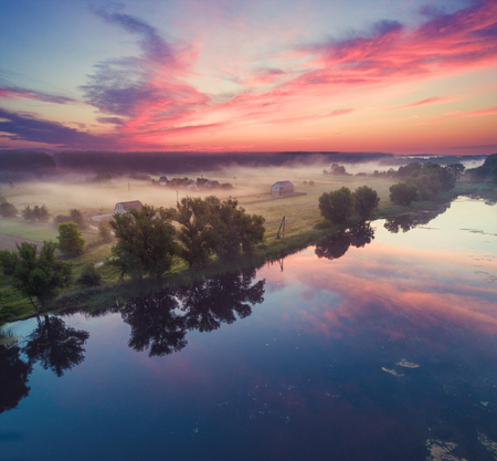 Aerial view of countryside and river in early misty morning. The time before sunrise. View from above