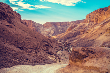 The dirt road among the mountains in the desert. Israel. The beginning of the ascent to Masada from the west side