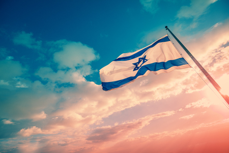 Flag of Israel against the morning sky. The Israeli flag on Masada
