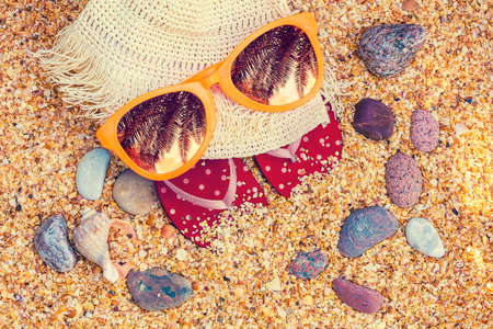 Beach scene. Sun straw hat, flip-flop sandals, and sunglasses with palm tree reflection lying on sea coquina shells on the beach