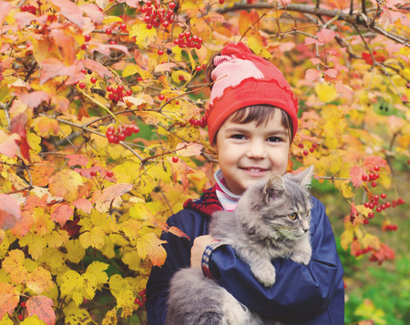 Little girl hugging a cat in the garden in autumn