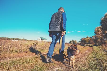 A man with a Labrador retriever dog walks along a rural road in autumn