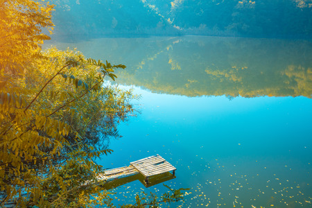 Beautiful mountain lake in the fall. Reflection of a mountain in the water of the lake. Wooden pier on the water