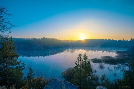 Sunrise over the lake in the forest. Foggy morning