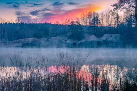 Early misty morning. Sunrise over the lake with the rocky shore Imagens - 112442600