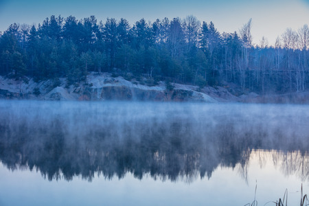 Early misty morning. Dawn over the lake with the rocky shore 免版税图像