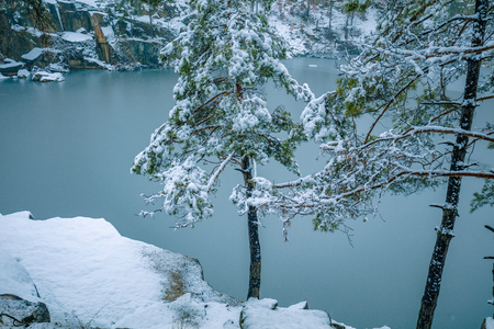 Beautiful rocky lake with pine trees. Lake in the winter in snowfall Stock Photo