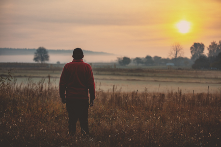 Man standing in the field early in the morning and looking at the sunrise
