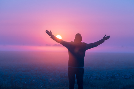 A man with his hands in the air stands in the field in the early morning and looks at the sunrise