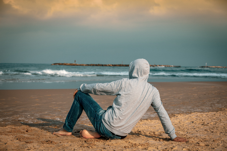Man barefoot sitting on the beach and looking at the sea Stok Fotoğraf
