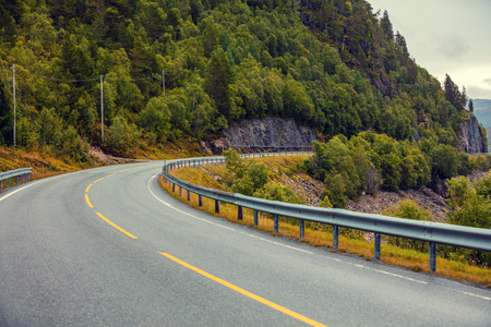 Driving a car on a winding mountain road. View of mountain road from the windshield. Nature of Norway
