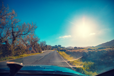 Driving a car on a mountain road on a sunny day. View from the windshield of the beautiful nature of Spain.