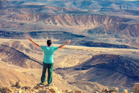 A man with hands in the air standing on the cliff in the desert Imagens