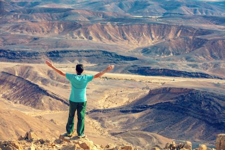 Ein Mann mit Händen in der Luft, der auf der Klippe in der Wüste steht