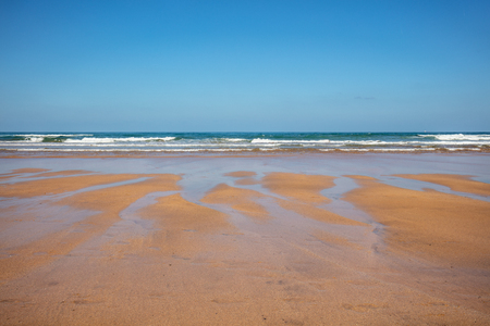 Sandy beach at low tide. Ocean on a sunny day Stock Photo