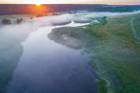 Early misty morning, sunrise over the lake. Rural landscape in summer. Aerial view