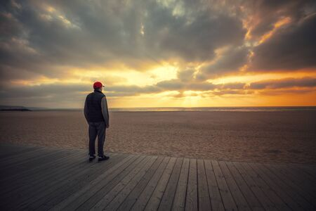 Silhouette of man on the beach looking at magical dramatic sunset. The man standing on the wooden terrace