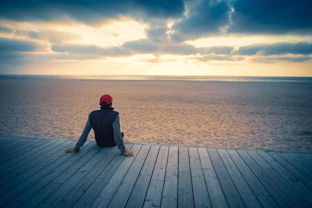 Silhouette of man on the beach looking at magical dramatic sunset. The man sitting on the wooden terrace Фото со стока