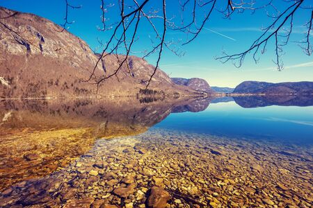 Rocky shore of the mountain lake. Beautiful nature. Reflection on the lake