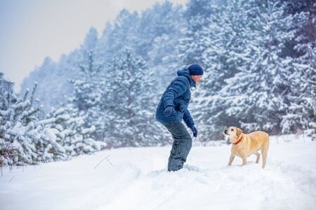 A man and dog are best friends. The man with the dog playing in a snowy pine forest in winter