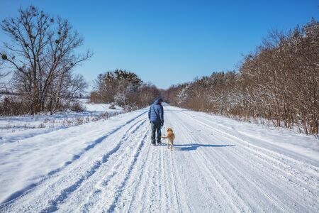 Man with the dog on a leash walks in a snowy road in winter Фото со стока