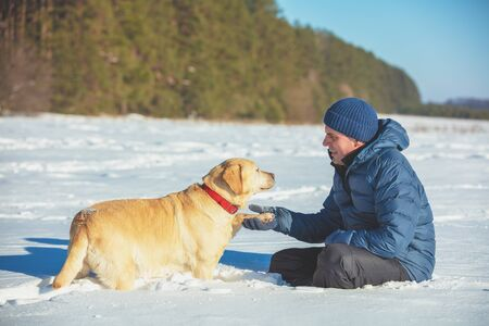 A human and dog are best friends. The man with the dog sitting in a snowy field in winter. Trained Labrador retriever dog extends the paw to the man