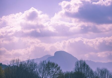 Silhouette of a mountain range against the background of a beautiful cloudy sky Фото со стока