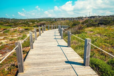 The wooden stairway at the rocky seashore on a sunny day. Polvoeira the beach. Pataias, Portugal, Europe