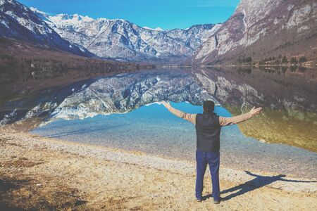 Man with hands in the air standing on the shore of the mountain lake in early spring. Bohinj lake, Slovenia, Europe Zdjęcie Seryjne